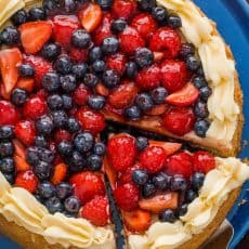"""Our spin on the classic German Fruit Cake """"Obstkuchen Obsttorte"""". It has a super soft cake base, is loaded with glazed berries and a secret ingredient stabilized whipped cream frosting! 
