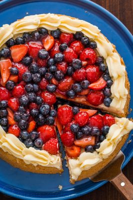 "Our spin on the classic German Fruit Cake ""Obstkuchen Obsttorte"". It has a super soft cake base, is loaded with glazed berries and a secret ingredient stabilized whipped cream frosting! 
