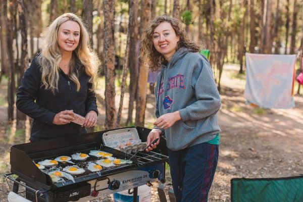 Two woman at the stovetop cooking sunny side up eggs