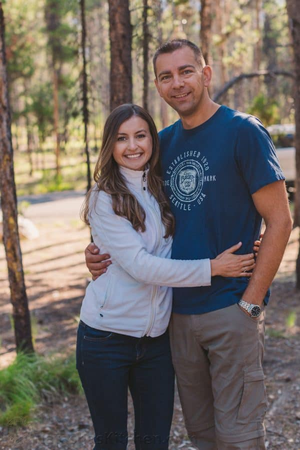 A couple standing in front of trees
