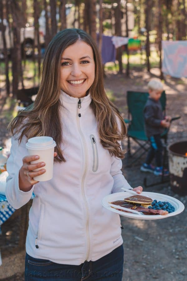 Natasha Kravchuk holding a cup, with Camping and Tent