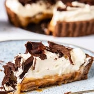 A close-up of a Banoffee pie slice on a blue plate.