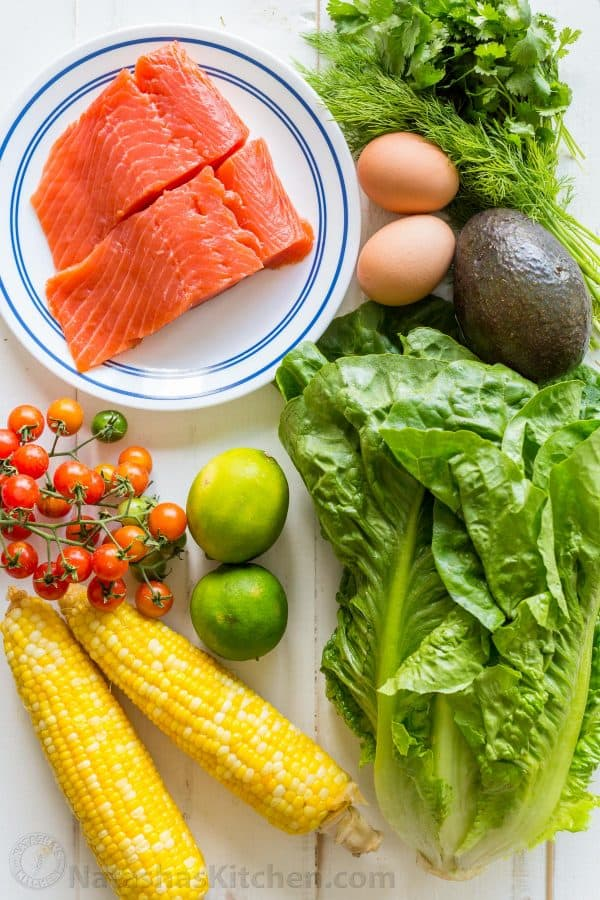 Ingredients for Cobb Salad with Salmon, avocado, lettuce, tomatoes, corn and cilantro lime dressing