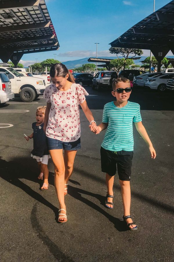 A mother and two children holding hands and walking in a parking lot