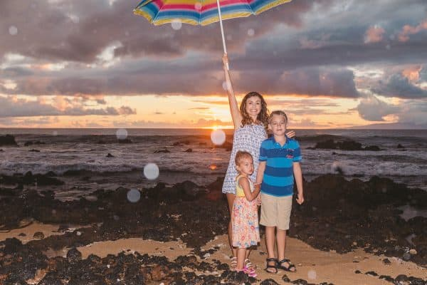 A mother and two children standing at the beach with the mother holding an umbrella