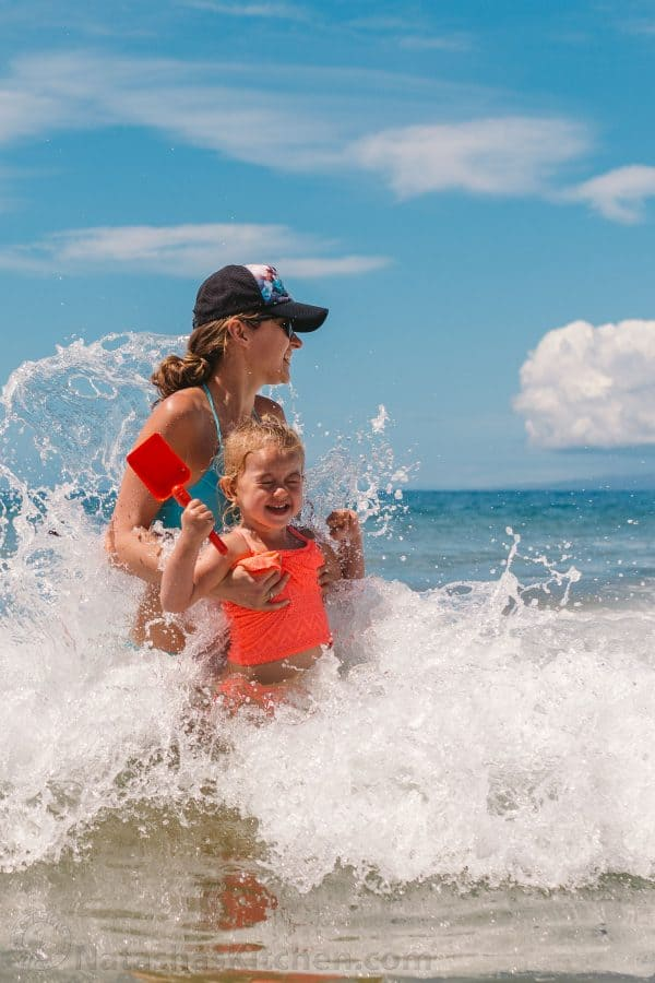 A young girl with her mother holding her riding a wave with a shovel in hand
