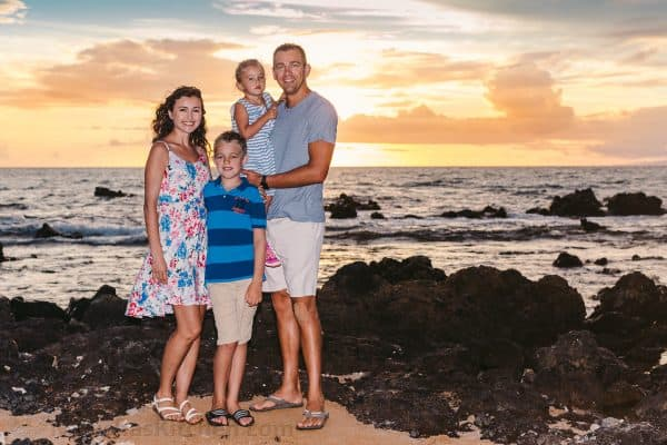 A family standing on a beach at sunset