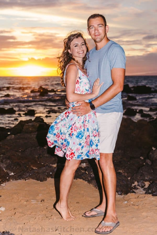 A photo of a couple standing at the beach at sunset