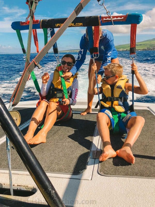 A mother and son being strapped in to go parasailing
