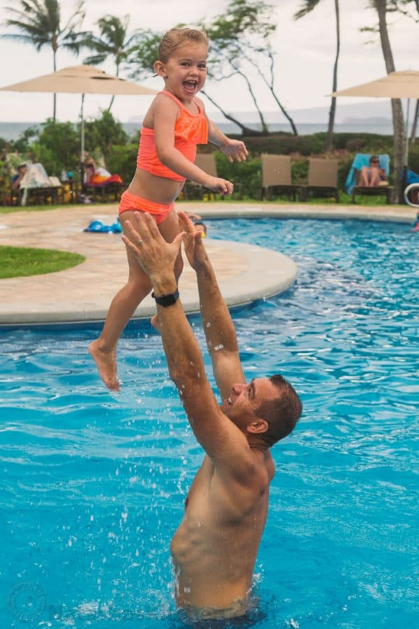 A father tossing his daughter in the air in a pool