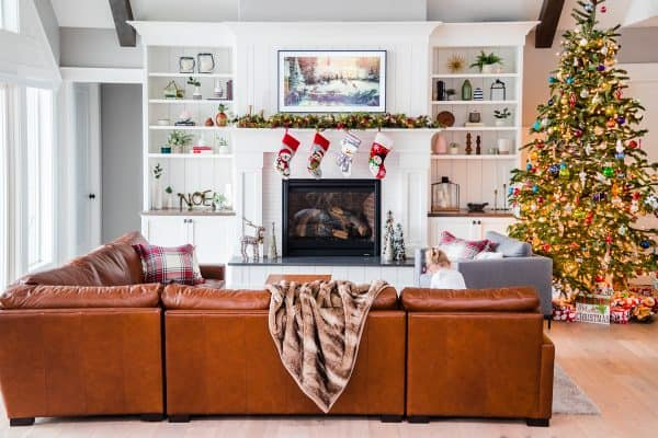 A living room filled with furniture, a fireplace and Christmas tree