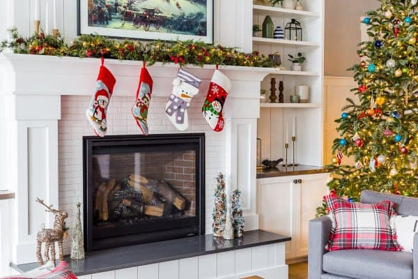 A fire place with four stockings hanging off and Christmas decorations around it