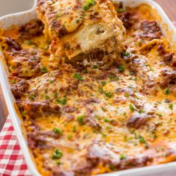 This EASY Lasagna Recipe is beefy, saucy and supremely flavorful. Homemade lasagna is better than any restaurant version and it feeds a crowd.