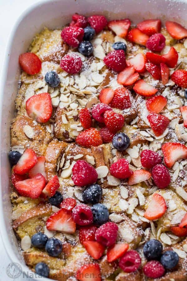 French Toast Casserole bread with almonds and berries in a baking dish.