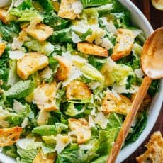 Caesar Salad recipe in a bowl with romaine, croutons, parmesan cheese and caesar dressing