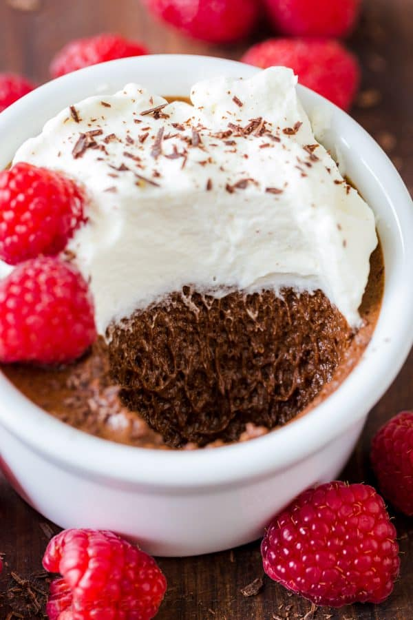 Chocolate mousse in a cup with whipped cream, shaved chocolate and fresh raspberries