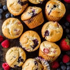 Fluffy and moist Mixed Berry Muffins come together quickly and are loaded with juicy strawberries, raspberries and blueberries. Easy, excellent berry muffin recipe! #muffins #berrymuffins #strawberrymuffins #blueberrymuffins #raspberrymuffins #berrymuffinrecipe #howtomakemuffins #easymuffins #breakfastmuffins #natashaskitchen #dessert #berries #triberrymuffins #tripleberrymuffins #strawberries #blueberries #raspberries