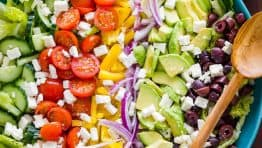 Greek salad ingredients arranged in mixing bowl with greek salad dressing on the side