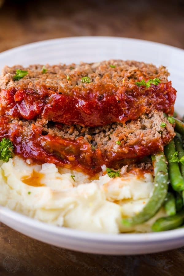 Meatloaf served on a plate with potatoes and greens and garnished with parsley