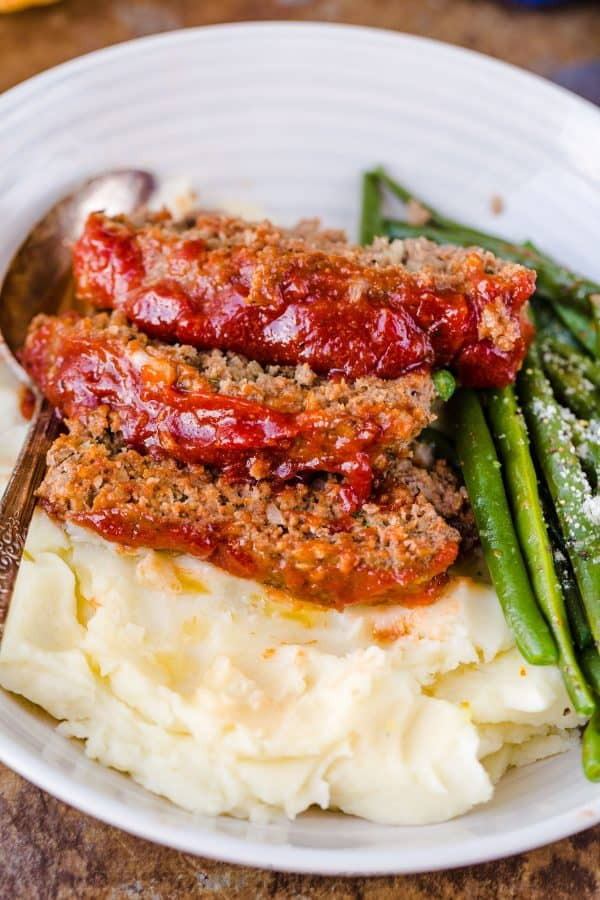 Meatloaf recipe sliced and served on a plate with mashed potatoes and vegetables