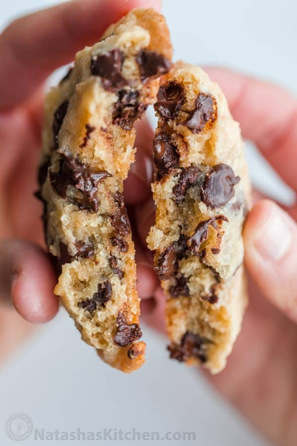 Soft chocolate chip cookies broken in half to show moist chocolatey center