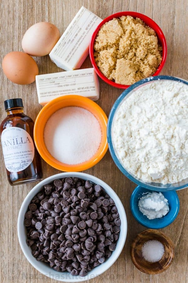 Ingredients for chocolate chip cookies with baking soda, brown sugar, chocolate chips, butter and eggs