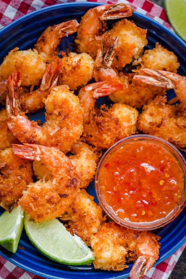Coconut Shrimp recipe arranged on a platter served with sweet chili sauce and fresh lime wedges
