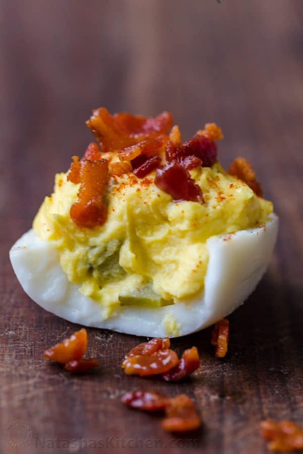 Deviled Egg stuffed with an egg yolk, dill pickle and mustard filling, garnished with bacon