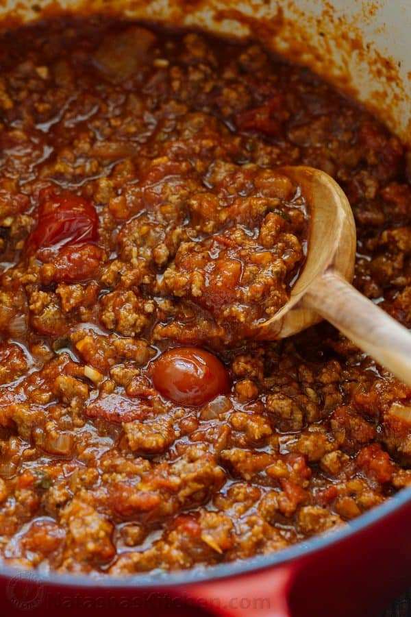 A close up of meat sauce for spaghetti with a wooden spoon in the pot.