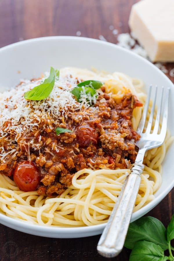 Spaghetti meat sauce in a bowl of spaghetti garnished with parmesan cheese and basil