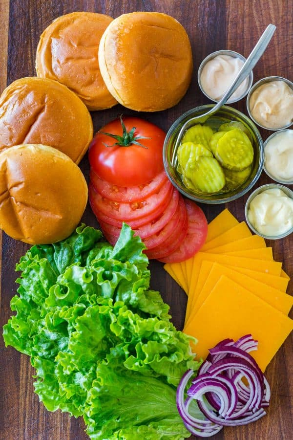 Classic burger toppings with buns, tomatoes, lettuce, cheese, pickles, red onion and sauces