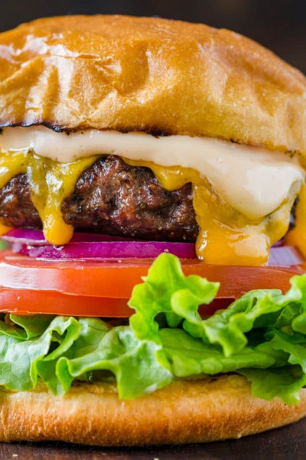 Juicy burger recipe up close shot with cheese, burger sauce and toppings inside a bun