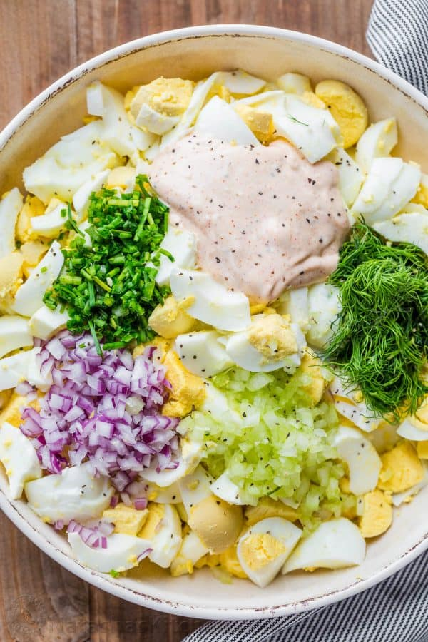Boiled egg, onion, celery, dill salad ingredients cubed in a bowl for Egg Salad.
