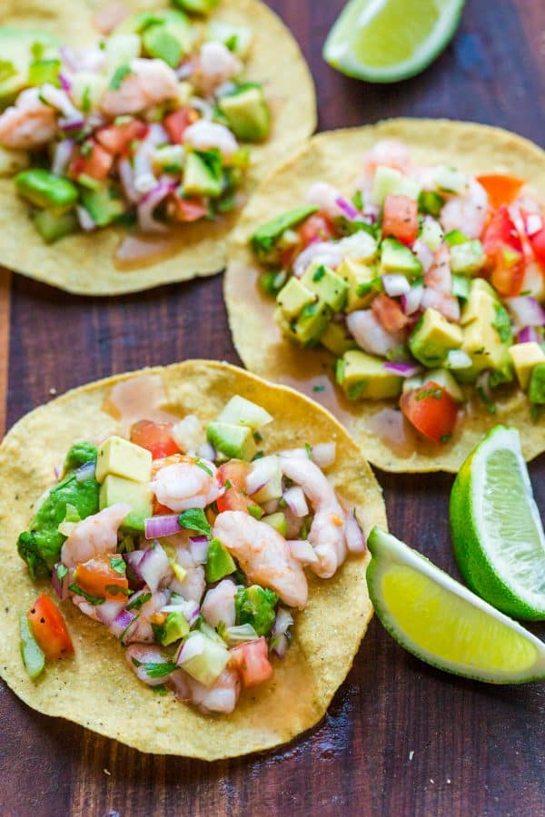 Shrimp ceviche served on tostadas with lime wedges