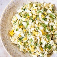 Potato salad sprinkled with dill in beige bowl