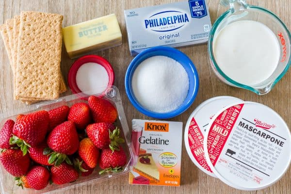 Ingredients for strawberry cheesecake with strawberries, cream cheese, cream, mascarpone, gelatin, graham crackers and butter