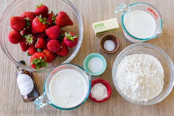 Ingredients for strawberry shortcake with strawberries, cream, flour, vanilla, butter, cream, and milk