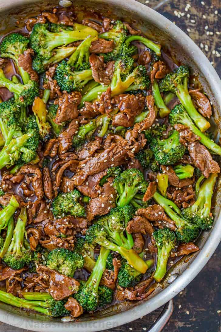 Beef and broccoli recipe in fry pan garnished with sesame seeds