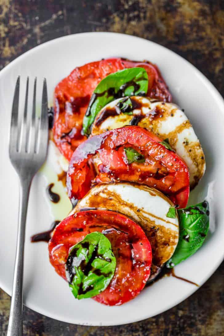 Morceau de salade caprese sur une assiette avec fromage mozzarella, tomates, basilic et garni de sauce balsamique et d'huile d'olive extra vierge.
