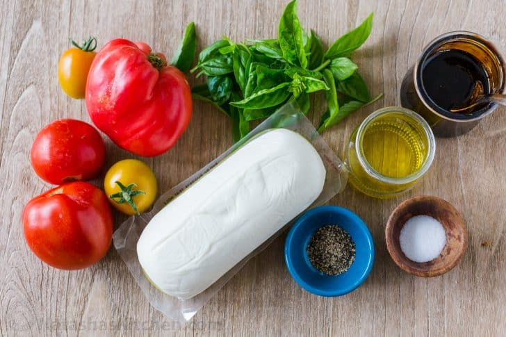 Ingredients to make salad with tomatoes, mozzarella, basil, extra virgin olive oil, salt, pepper, and balsamic glaze