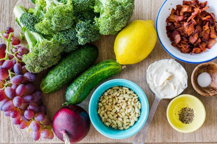 Ingredientes para ensalada de brócoli y uvas con brócoli, pepino, uvas, tocino, cebolla morada y aderezo