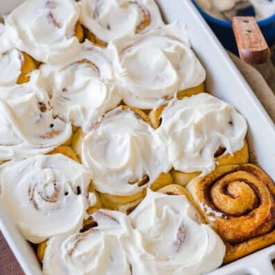 cinnamon rolls in casserole dish with icing on top