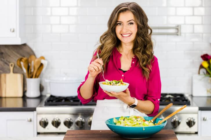 Natasha holding a bowl of Greek salad in a kitchen