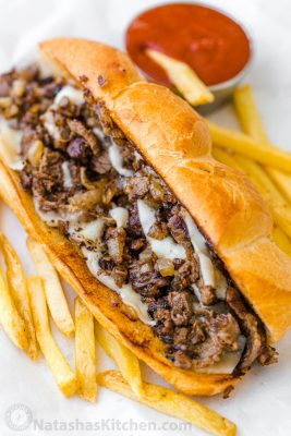 Philly cheesesteak served on hoagie roll with fries and ketchup