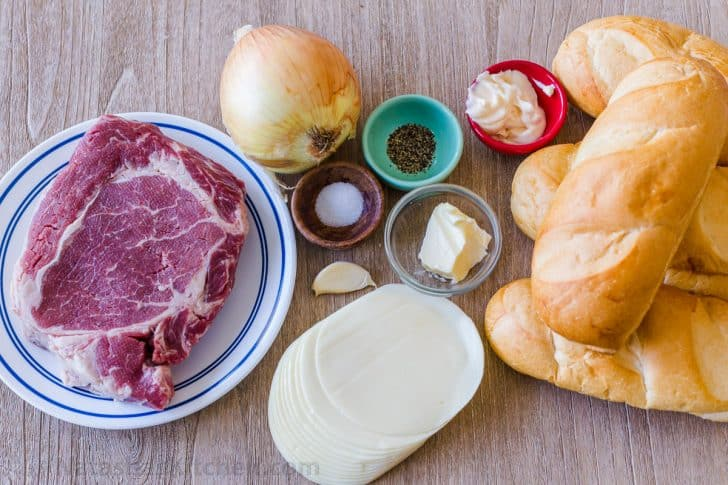 Ingredients for philly cheesesteak sandwich including ribeye steak, hoagie rolls, provolone cheese, onion, mayo, garlic butter