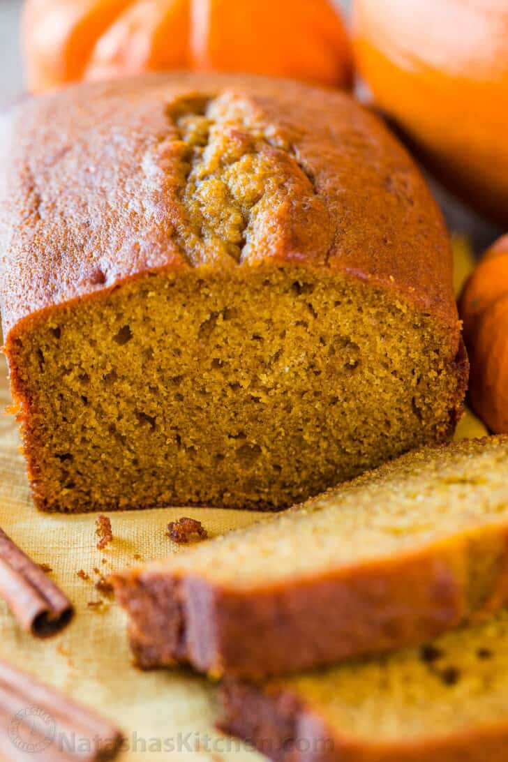 Sliced pumpkin bread with pumpkins in background
