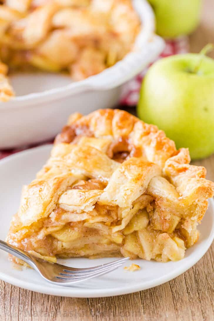 Apple pie slice on a plate with apples in background