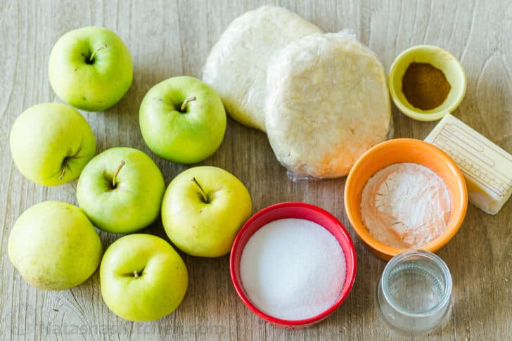 Crust for pie with ingredients to make pie including apples, sugar, flour, butter, cinnamon