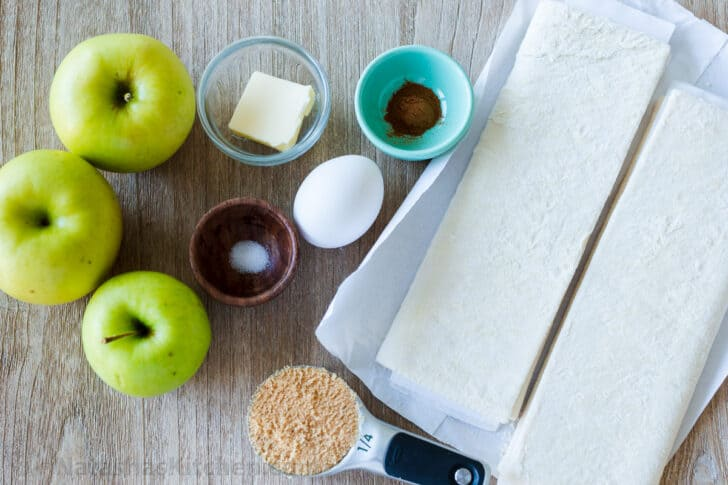 Ingredients for apple turnovers with puff pastry, granny smith apples, butter, egg, sugar, salt and cinnamon