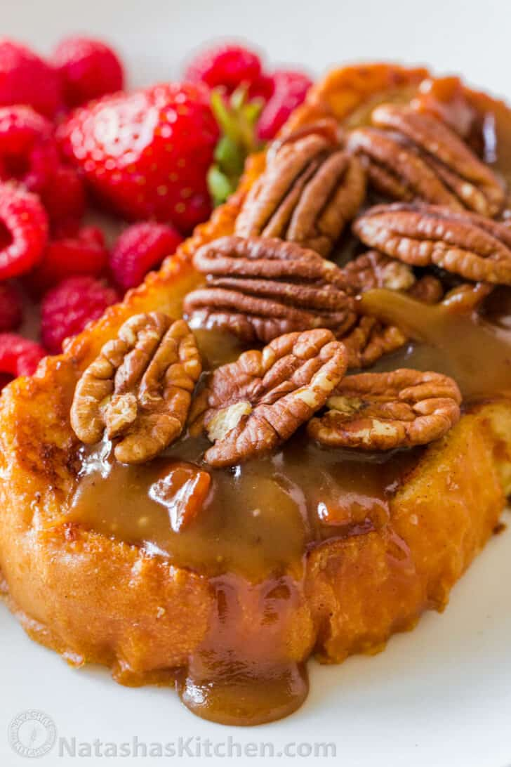 Assembled slice of French toast topped with caramel and pecans